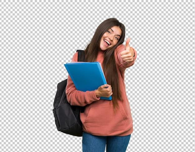 Giovane donna dello studente che tiene i taccuini con i pollici su perché è successo qualcosa di buono Psd Premium