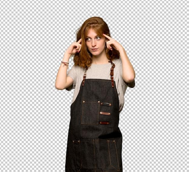 Giovane donna di redhead con il grembiule che ha dubbi e pensiero Psd Premium