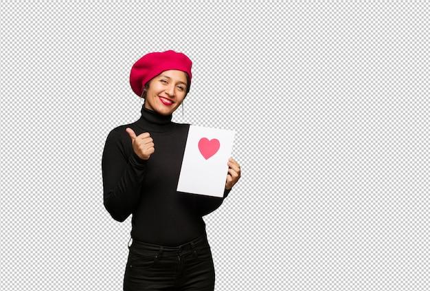 Giovane donna nel giorno di san valentino che sorride e che alza pollice in su Psd Premium