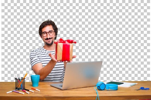 Giovane grafico pazzo su una scrivania con un computer portatile e con il concetto di scatola regalo Psd Premium