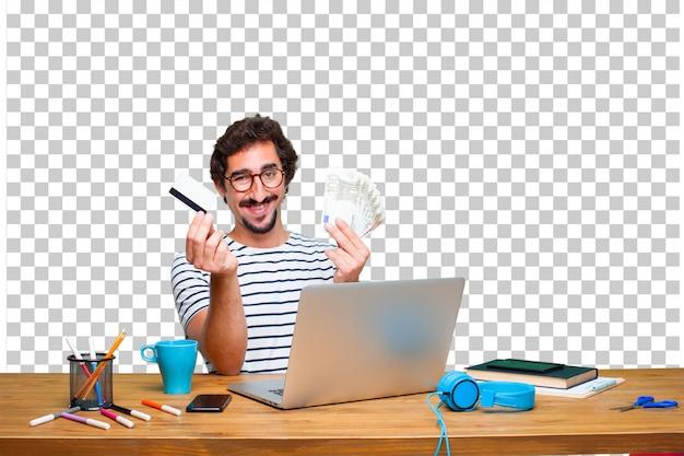 Giovane grafico pazzo su una scrivania con un concetto di laptop e paga, acquisto o denaro Psd Premium