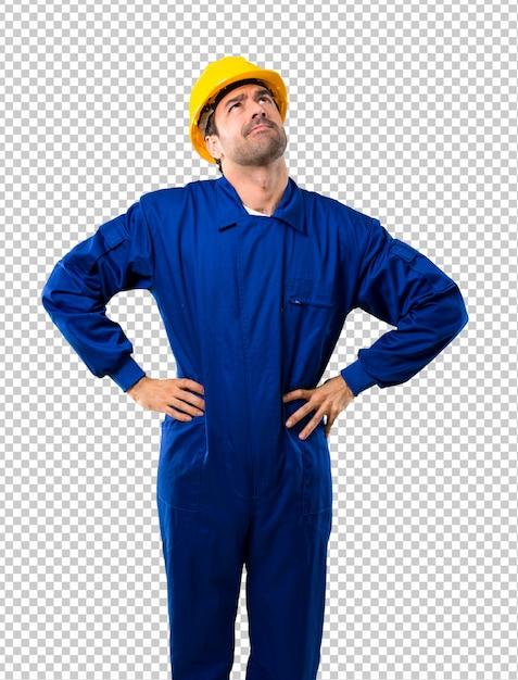 Giovane operaio con stand casco e alzando lo sguardo Psd Premium