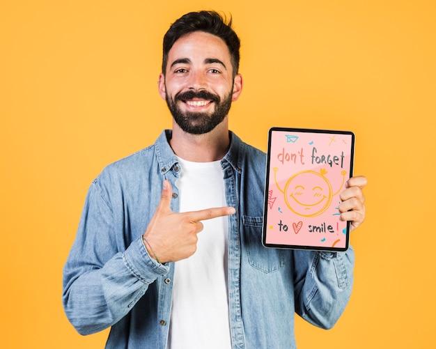 Giovane sorridente che indica dito a derisione della compressa su Psd Gratuite