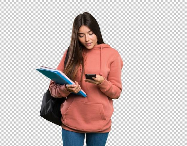 Giovani taccuini della tenuta della donna dello studente che inviano un messaggio con il cellulare Psd Premium