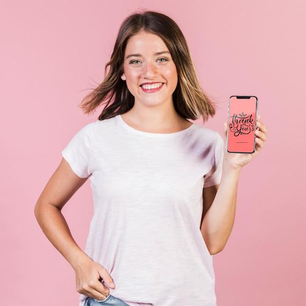 Glimlachende jonge vrouw die een cellphonemodel houdt Gratis Psd