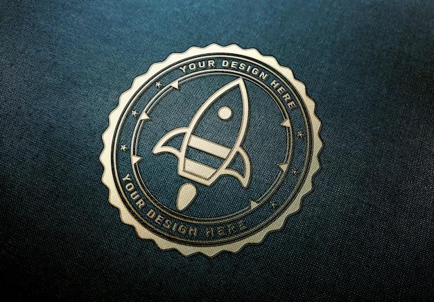 Gouden logo mockup op donkere stof textuur Premium Psd