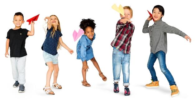 Grupo diverso de niños lanzando avión de papel PSD Premium