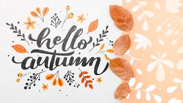 Hallo herfst belettering naast bruine bladeren patroon Gratis Psd