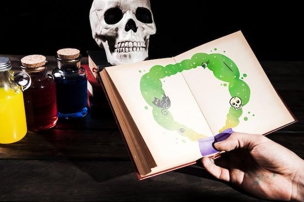 Hand met boek met tekeningen en flessen gif Gratis Psd