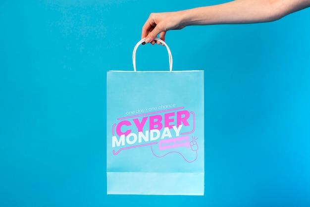 Hand met een cyber maandag papieren zak Gratis Psd