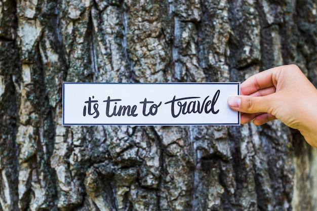 Hand met papier in de natuur voor reizen concept Gratis Psd