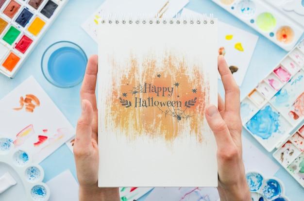 Handen die notitieboekje met halloween-bericht houden Gratis Psd