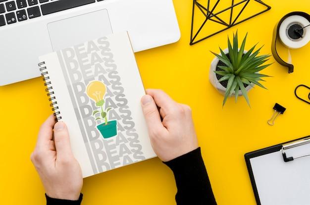 Handen die notitieboekjemodel over bureau houden Gratis Psd