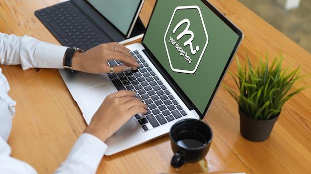 Handen typen op mockup laptop toetsenbord in de buurt van koffiekopje Premium Psd