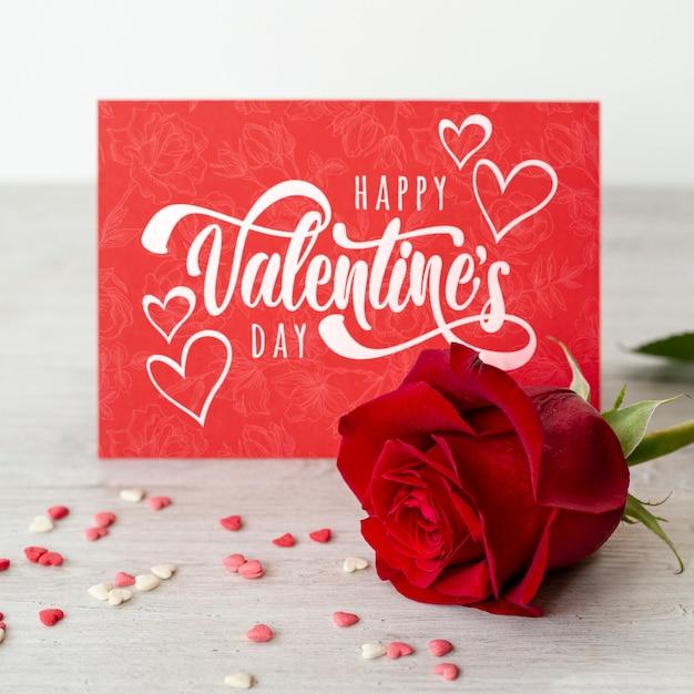 Happy valentijnsdag belettering op rode kaart met rode roos Gratis Psd