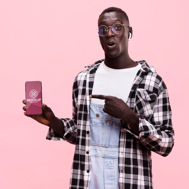 Hermoso hombre con maqueta de teléfono inteligente PSD gratuito