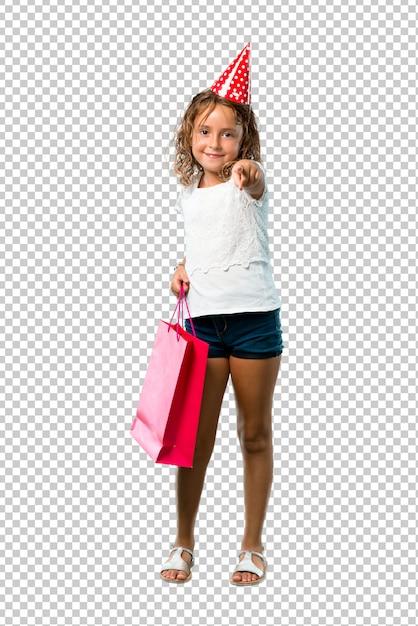 Het meisje bij een verjaardagspartij die een giftzak houdt richt puntenvinger op u Premium Psd