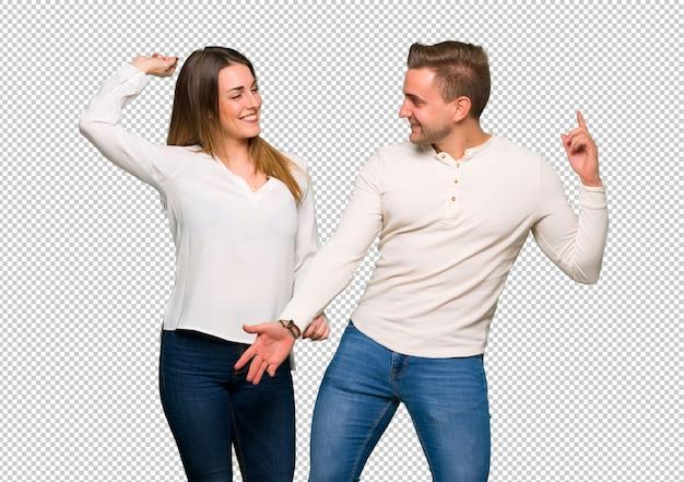 Het paar in valentijnskaartdag geniet van dansend terwijl het luisteren aan muziek op een partij Premium Psd