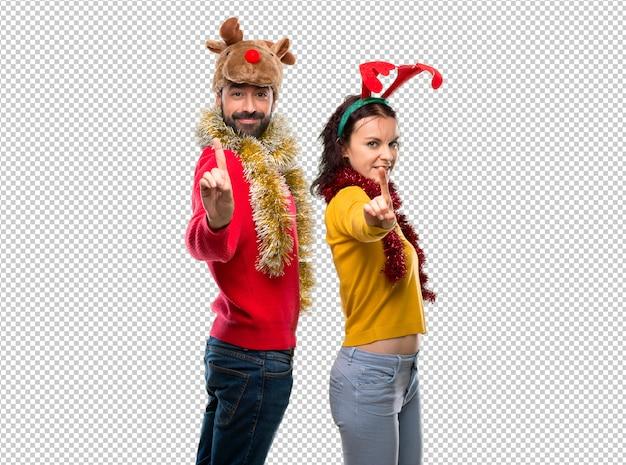 Het paar kleedde zich omhoog voor de kerstmisvakantie die en een vinger in teken van het beste toont opheffen Premium Psd
