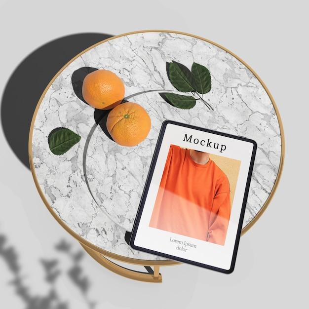 Hoge hoek van tablet op tafel met sinaasappelen en bladeren Gratis Psd