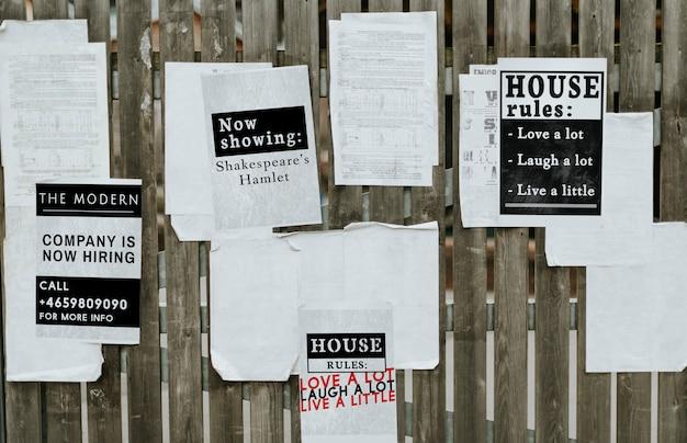 Hojas de anuncios de papel en una valla de madera. PSD gratuito