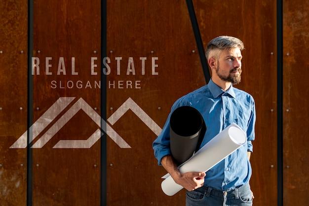 Hombre agente sosteniendo planes para nuevo edificio PSD gratuito