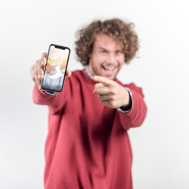Hombre alegre sujetando maqueta de smartphone PSD gratuito