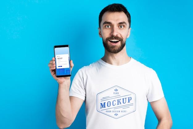 Hombre con camisa blanca mostrando tiro medio de teléfono móvil PSD gratuito