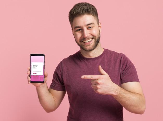 Hombre feliz mostrando maqueta digital de smartphone PSD gratuito