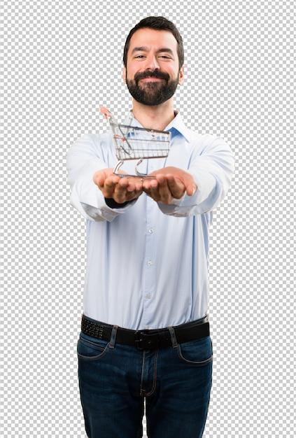 Hombre guapo feliz con barba sosteniendo un juguete de carrito de supermercado PSD Premium