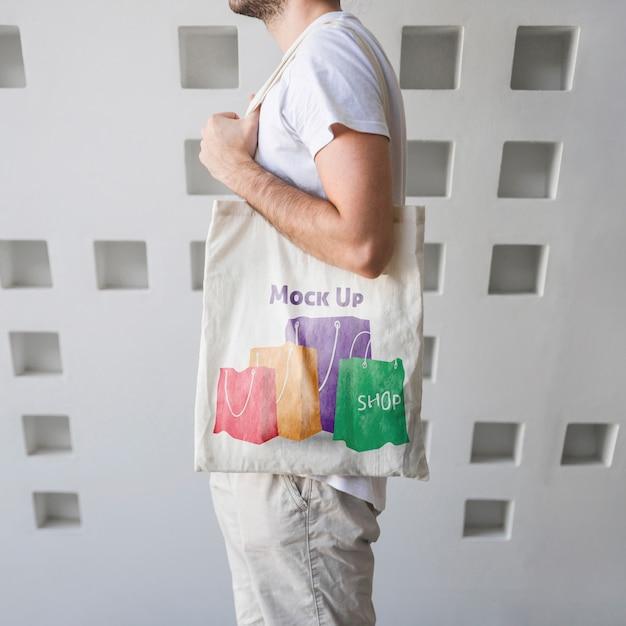Hombre joven con un mockup de bolsa PSD gratuito