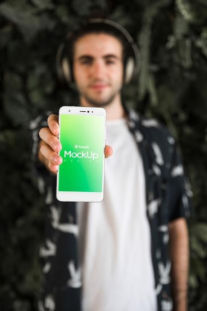 Hombre joven con un mockup de smartphone PSD gratuito
