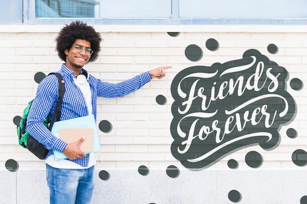Hombre joven sonriente que señala en el mensaje positivo PSD gratuito