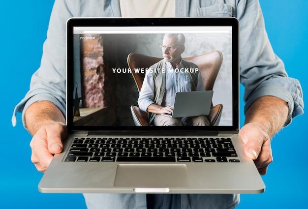Hombre mayor presentando maqueta de portátil PSD gratuito