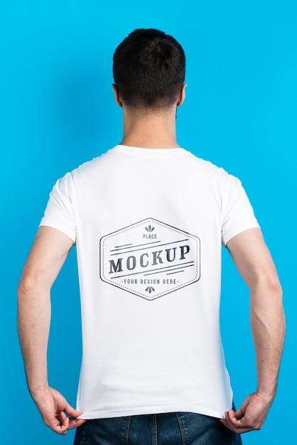 Hombre mostrando camiseta de maqueta desde atrás PSD Premium