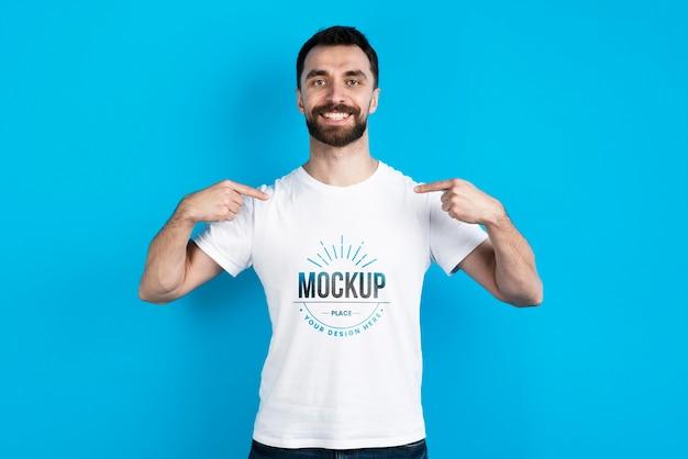 Hombre mostrando camiseta de maqueta PSD gratuito