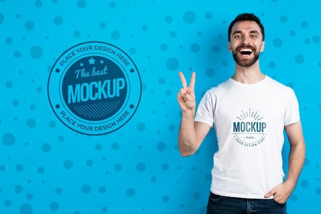 Hombre mostrando maqueta camisa signo de la paz PSD gratuito