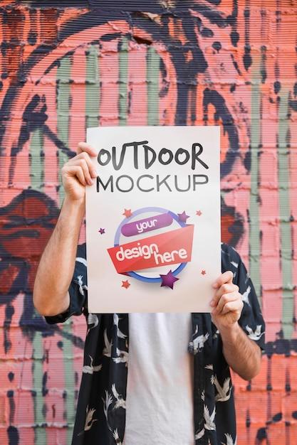 Hombre presentando mockup de cartel enfrente de muro de grafiti PSD gratuito