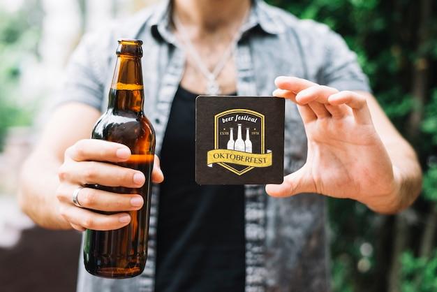 Hombre sujetando la botella de cerveza y posavasos PSD gratuito
