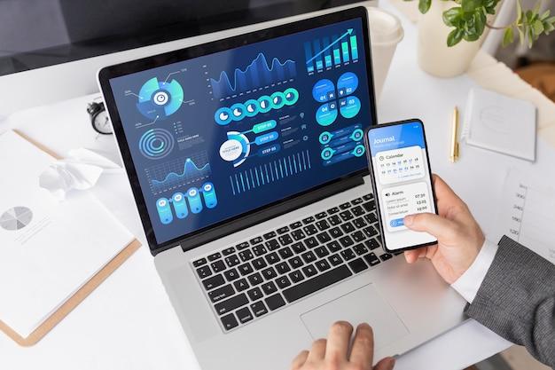 Hombre trabajando en el escritorio con maqueta portátil y teléfono PSD gratuito