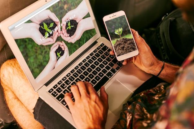 Hombre usando mockup de portátil y smartphone con concepto de naturaleza PSD gratuito