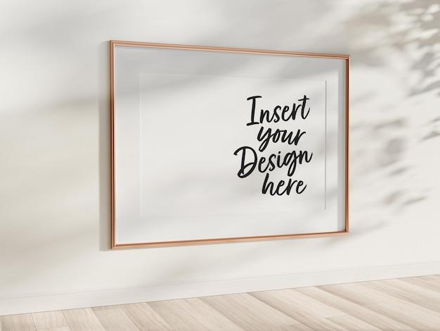 Horizontaal gouden frame dat op muurmodel hangt Premium Psd