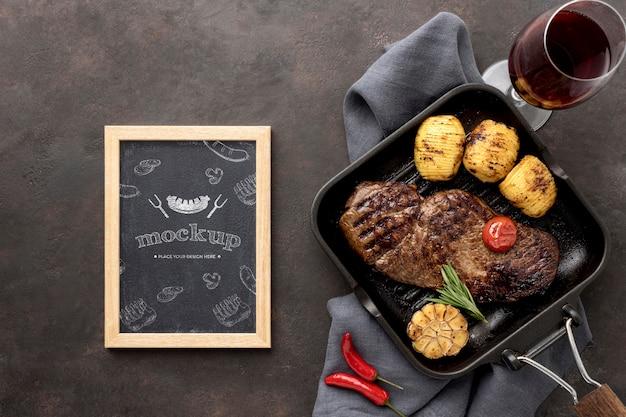 Houten bord met gegrild vlees op bureau Gratis Psd