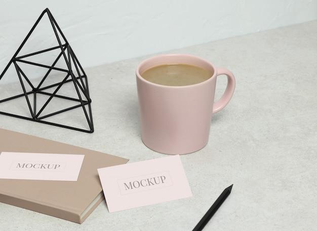 Il biglietto da visita modello su granito con libro rosa, matita nera e statuetta, tazza di caffè Psd Premium