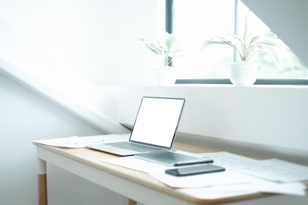 Imagen de la maqueta del portátil en la mesa de madera con el equipo del diseñador gráfico de la aplicación móvil PSD Premium