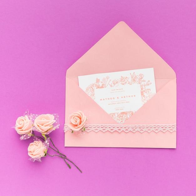 Invitación de boda y flores sobre fondo morado PSD gratuito