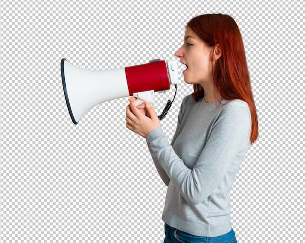 Jong roodharigemeisje die door een megafoon schreeuwen om iets in zijpositie aan te kondigen Premium Psd