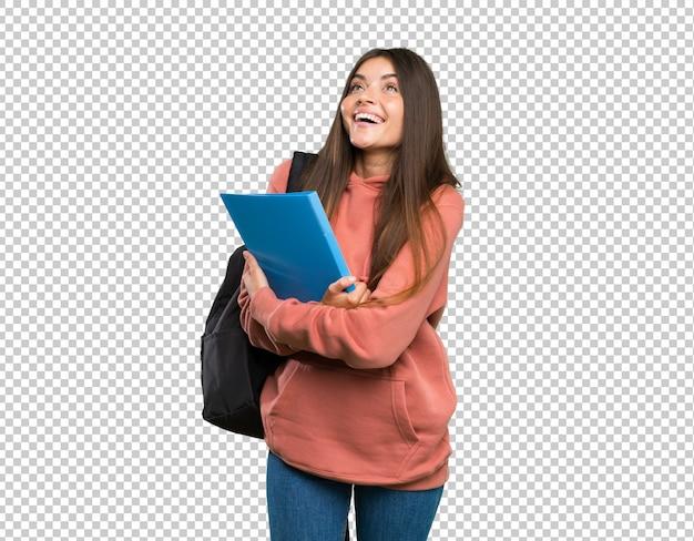 Jonge de holdingsnotitieboekjes die van de studentenvrouw omhoog terwijl het glimlachen kijken Premium Psd