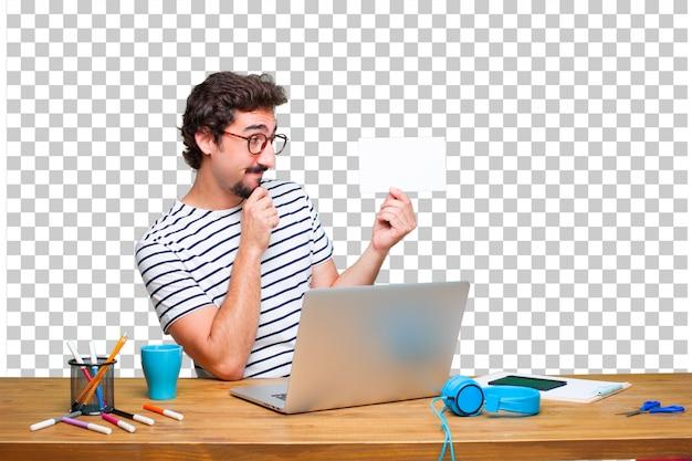 Jonge gekke grafische ontwerper op een bureau met laptop en met een aanplakbiljet Premium Psd