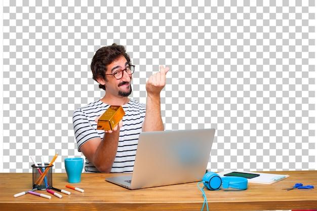 Jonge gekke grafische ontwerper op een bureau met laptop en met een gouden baar Premium Psd